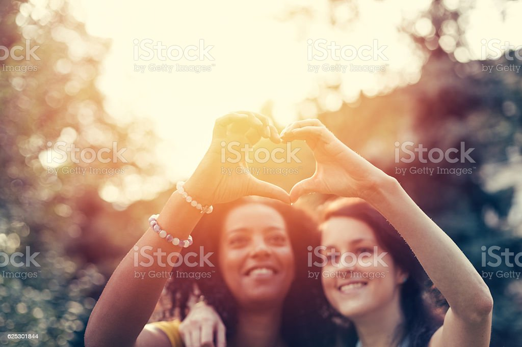 Mixed race girls showing heart symbol stock photo