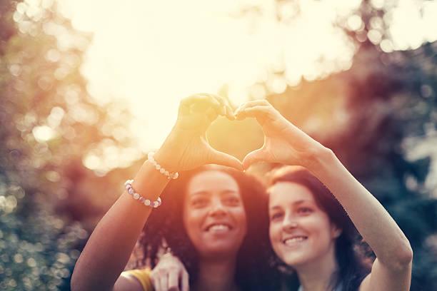 Mixed race girls showing heart symbol - Photo