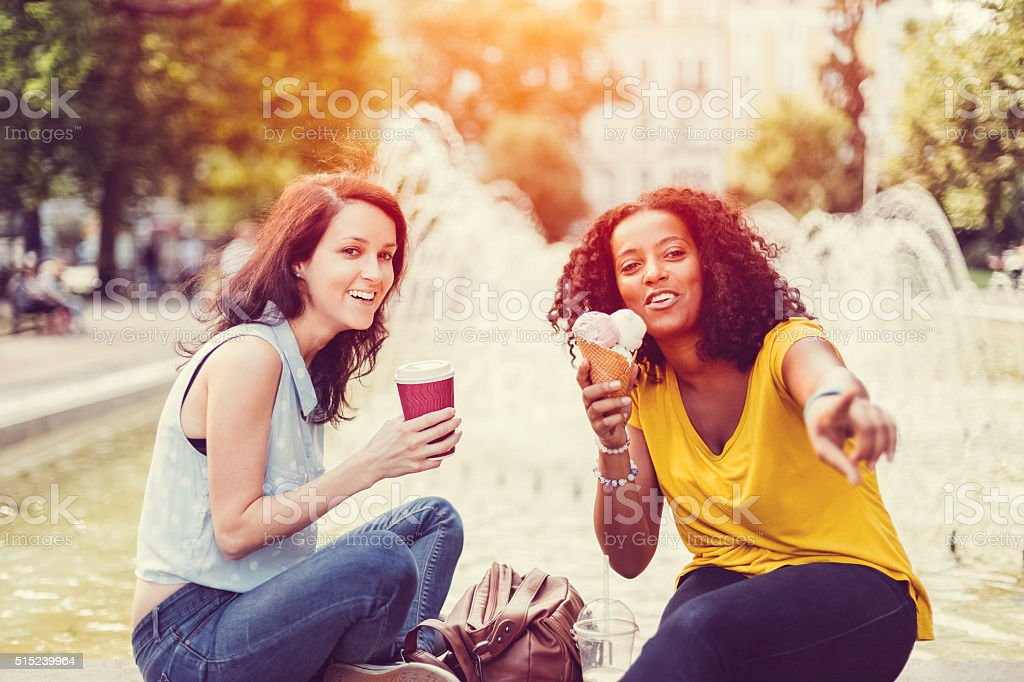 Mixed race girls talking and laughing stock photo