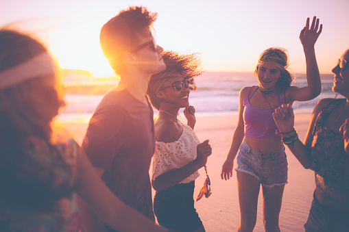 Mixed race group of joyful friends dancing together on a summer evening at a beachparty