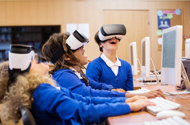 Mixed race group of students using virtual reality goggles stock photo