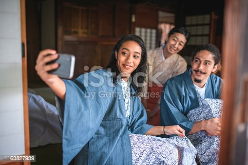 Male and female mixed race guests dressed in yukata posing for a selfie with Japanese server at traditional Tokyo ryokan.