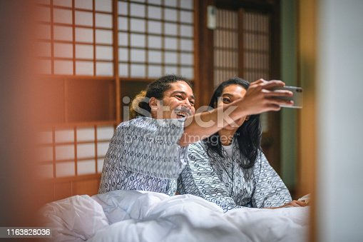 Laughing mixed race couple tucked into a cozy futon and creating a selfie at traditional Tokyo ryokan.