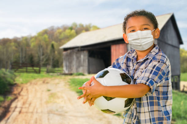 Mixed Race Hispanic and African American Boy Holding Soccer Ball Wearing Face Mask Outdoors stock photo