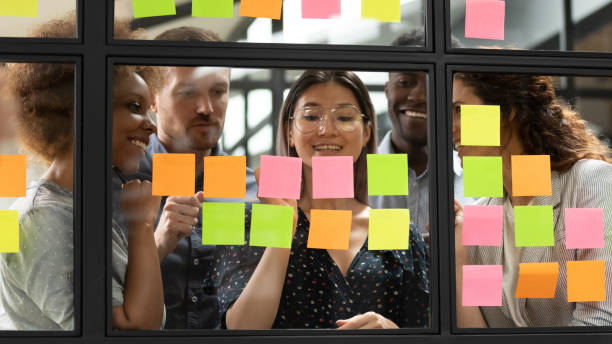 Mixed race interested young managers gathering near vietnamese team leader. Mixed race interested young managers group gathering near smiling vietnamese team leader, writing startup project details or tasks on colorful sticky notes, using kanban scrum methodology at office. agility stock pictures, royalty-free photos & images