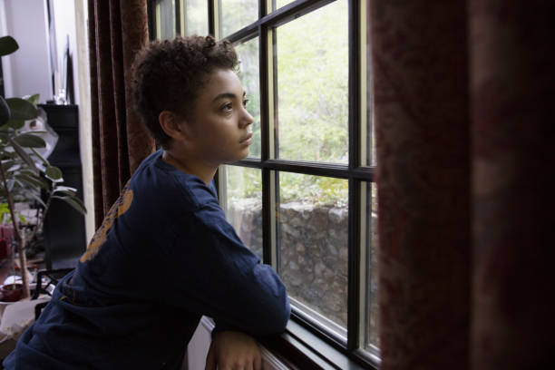 Mixed race kid looking through the window in lockdown