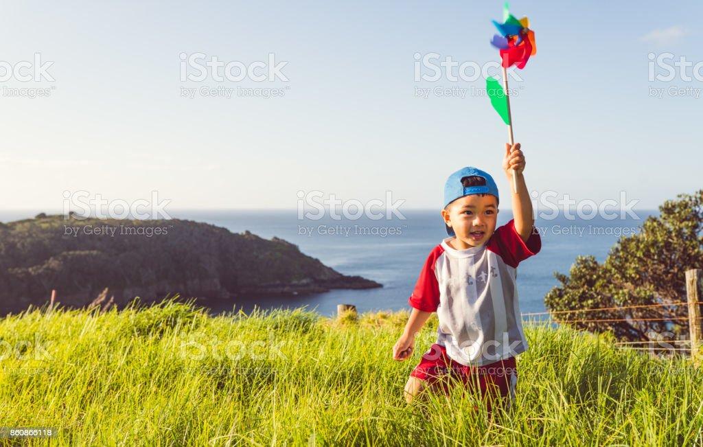 Mixed race kid with pinwheel in hand enjoying outdoor hike. stock photo