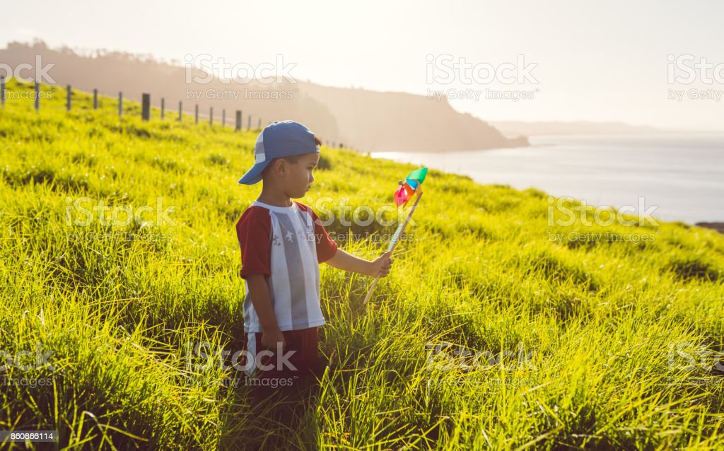 Mixed race kid with pinwheel in his hand. stock photo