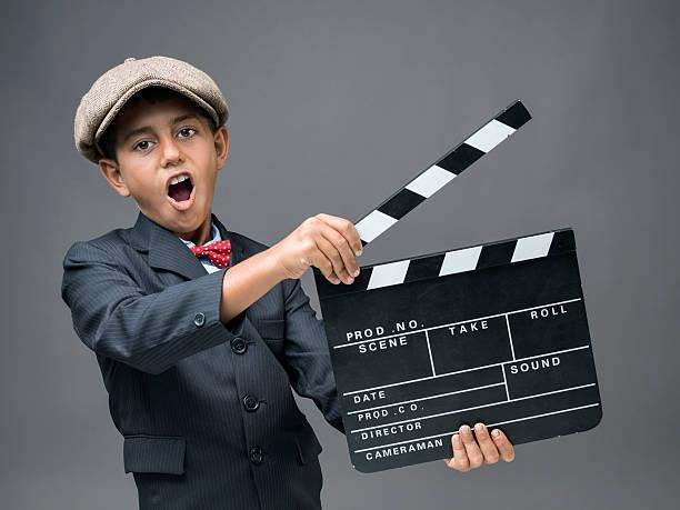 gemischtes kleine junge holding filmklappe und rufen - klappe hut stock-fotos und bilder