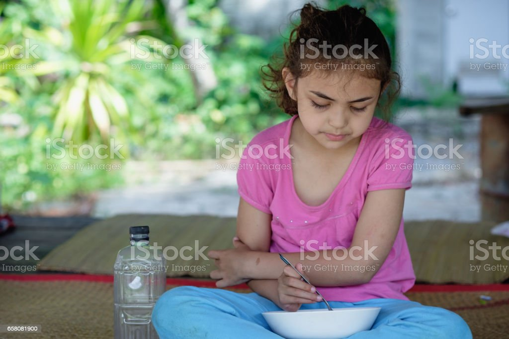 mixed race little girl eating meal at hut royalty-free stock photo