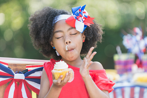A cute little mixed race 7 year old girl enjoying a cupcake at a July 4th or Memorial Day picnic. She is part Hispanic, Asian and black. The table and chair behind her are decorated in red, white and blue, celebrating American patriotism.