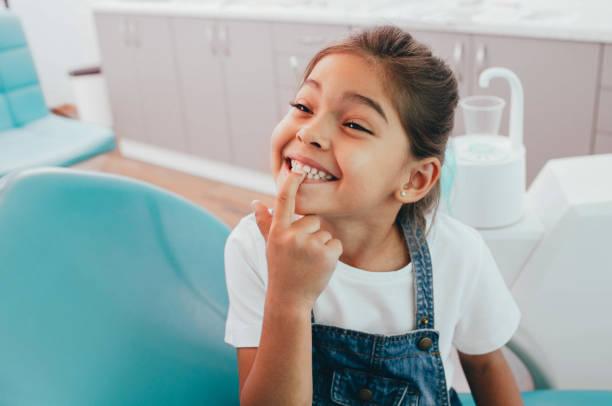 piccola paziente di razza mista che mostra il suo sorriso dento perfetto mentre si siede sedia dentisti - bambino foto e immagini stock