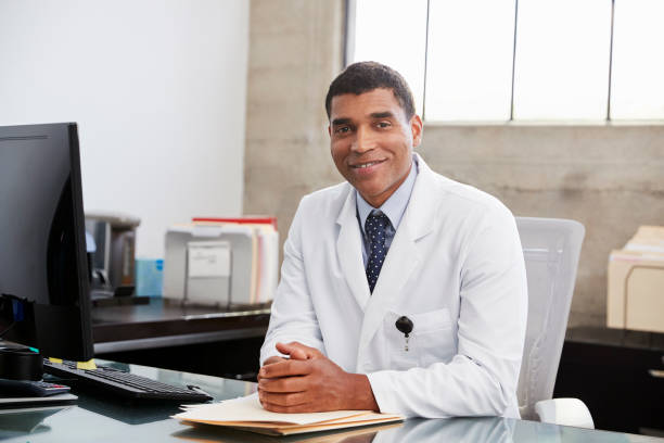 Mixed race  male doctor at desk, portrait Mixed race  male doctor at desk, portrait lab coat stock pictures, royalty-free photos & images