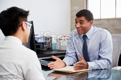 istock Mixed race male professional in meeting with young Asian man 1011794178