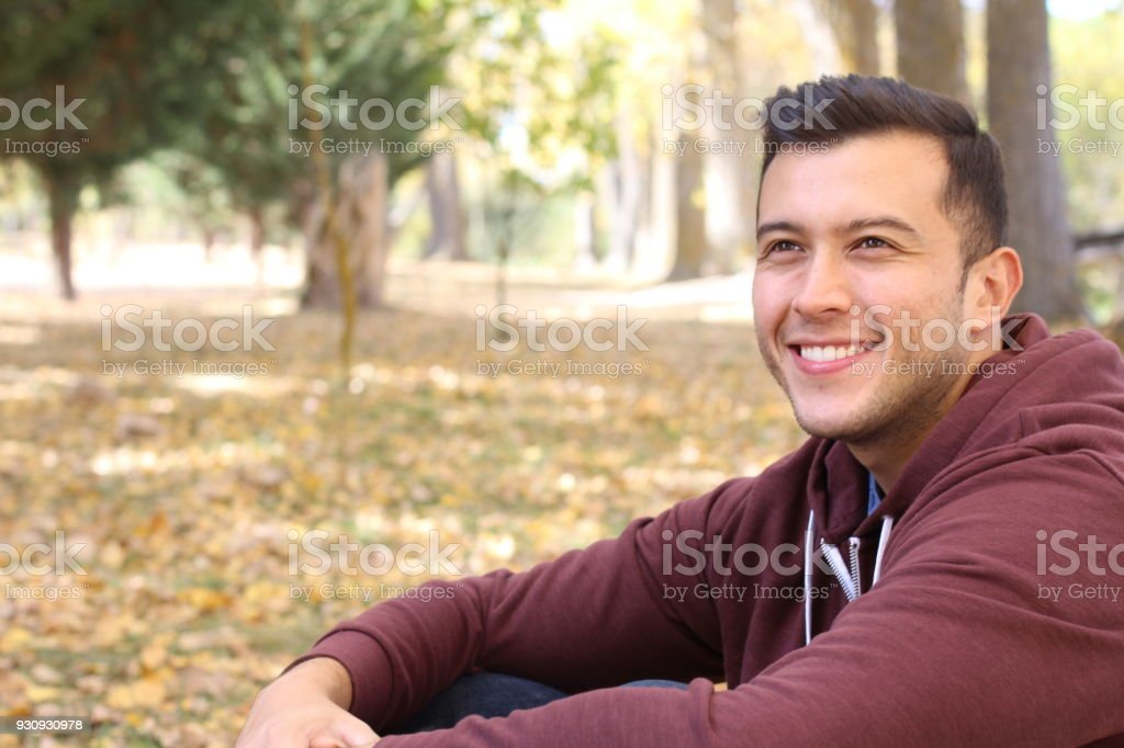 Mixed race male smiling in the fall with copy space stock photo