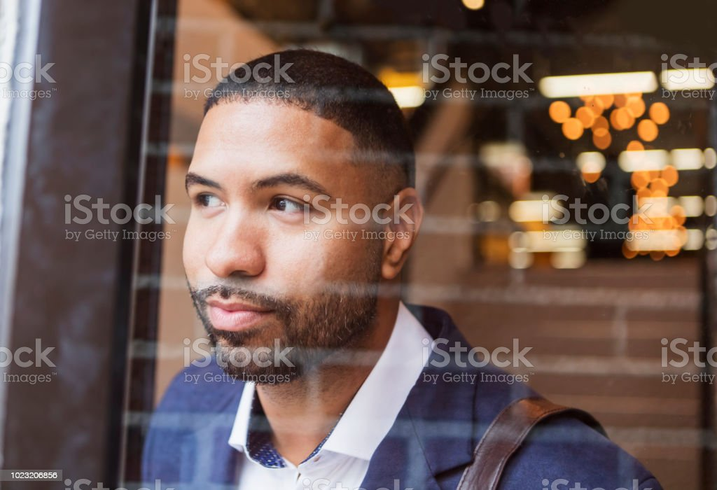 Mixed Race Man Leaving Work Looking Through Glass Door Stock Photo