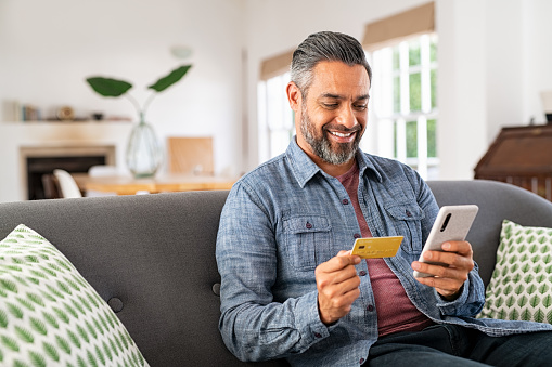 Middle eastern mature man with beard using credit card to make online payment on smartphone. Mixed race man holding debit card and using cellphone for shopping online from home. Smiling indian guy using smart phone to check credit card transactions from app.