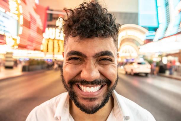 mixed race man with toothy grin facing camera - grandangolo tecnica fotografica foto e immagini stock