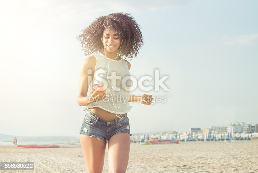 african curly hair girl running on beach listening to music with smart phone