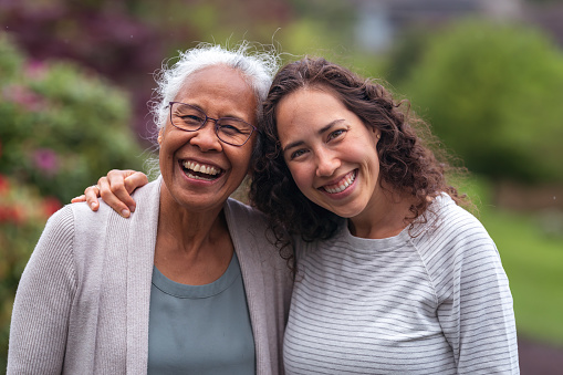 A senior woman embraces her millennial Eurasian daughter as they happily walk through a natural parkland area and enjoy their time together. The daughter is smiling at the camera.