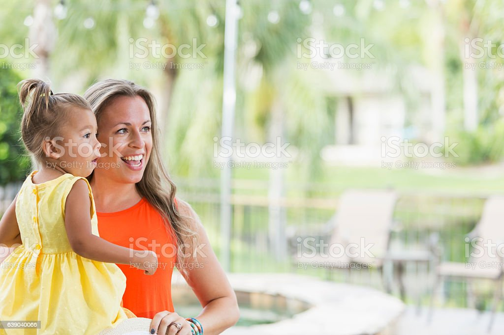 Mixed race mother and little girl watching in awe stock photo