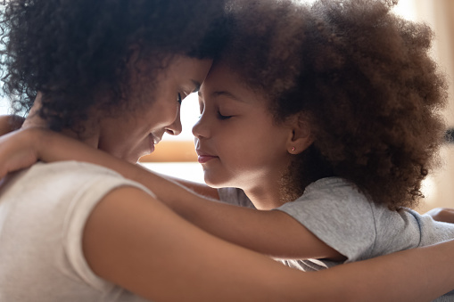istock Mixed race mother touching foreheads with little cute daughter. 1177334920