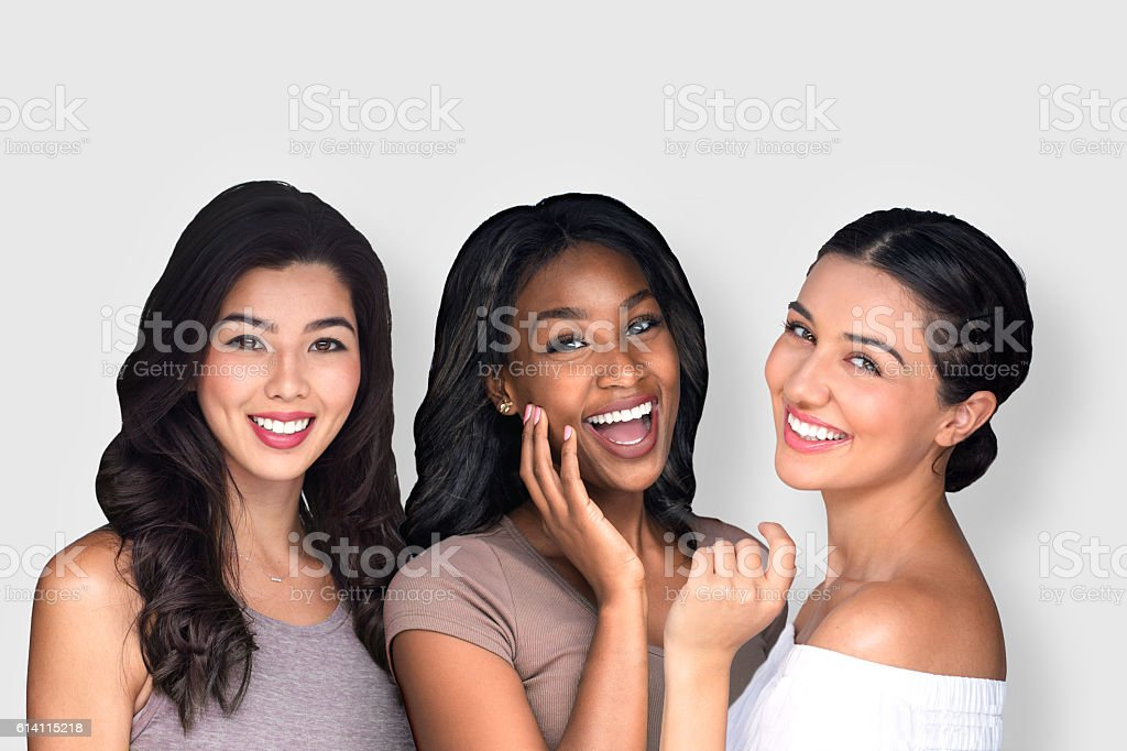Mixed race multi-ethnic female friends laughing together perfect smile - foto de acervo