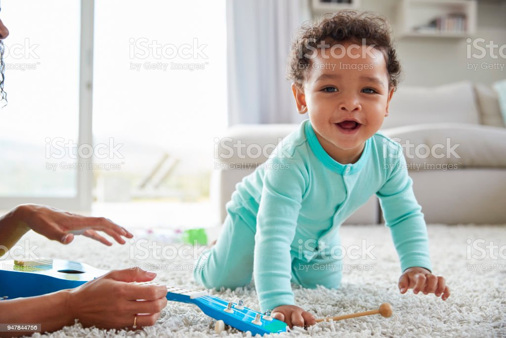 Mixed race mum and toddler son playing at home, close up stock photo