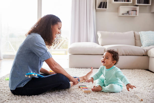 mixed race mum and toddler son playing in sitting room - sitting on floor stock photos and pictures
