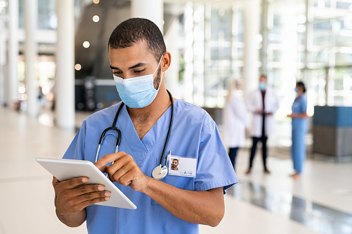 Young middle eastern nurse using digital tablet in corridor while wearing surgical mask. Busy mixed race doctor working on digital tablet and wearing protective face mask for coronavirus safety. Healthcare Indian worker in clinic taking notes on a patient's medical record with copy space.