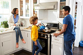 Mixed race parents and their daughter spending time together preparing food in the kitchen