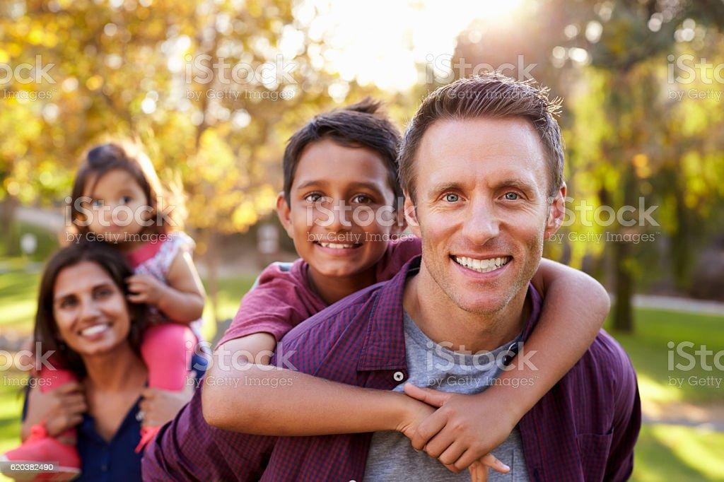 Mixed race parents carry kids piggyback, selective focus stock photo