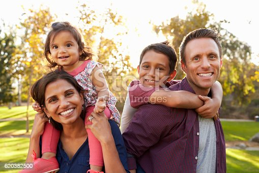 istock Mixed race parents carry their kids piggyback in a park 620382500