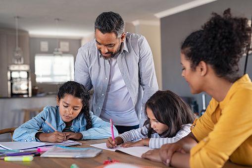 Indian parents helping children with their homework at home. Middle eastern father and african mother helping daughters studying at home. Little girls completing their exercises with the help of dad and mom, homeschooling concept.