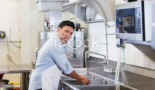 A mature mixed race Hispanic and Asian man working in a restaurant. He is standing in the kitchen at the sink, wearing an apron, looking at the camera as he washes his hands.