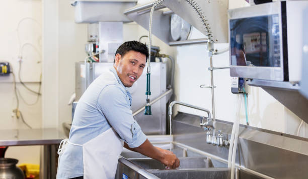 Mixed race restaurant worker in kitchen washing hands stock photo