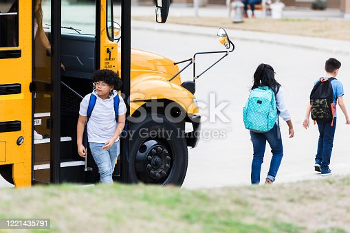 1031397608 istock photo Mixed race schoolboy getting off of school bus 1221435791