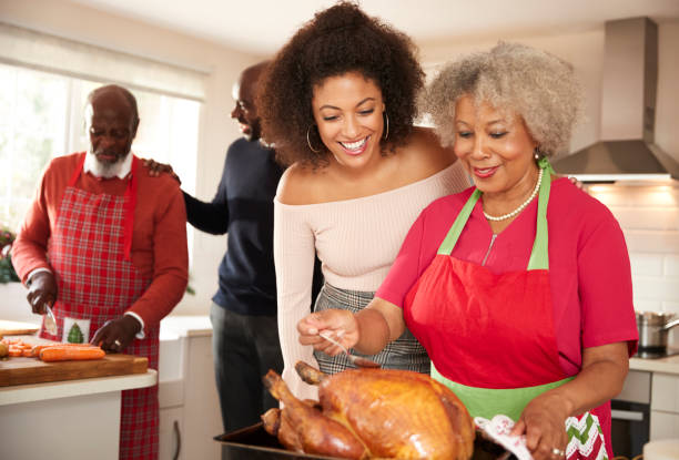 mixed race senior and young adult family members talking in the kitchen while preparing christmas dinner together, close up - christmas cooking imagens e fotografias de stock