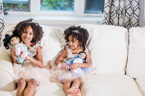 Two cute mixed race African-American and Hispanic girls, sisters 3 and 5 years old, playing together, sitting side by side on a sofa, holding dolls in their laps, wearing princess dresses and tiaras, smiling at the camera.