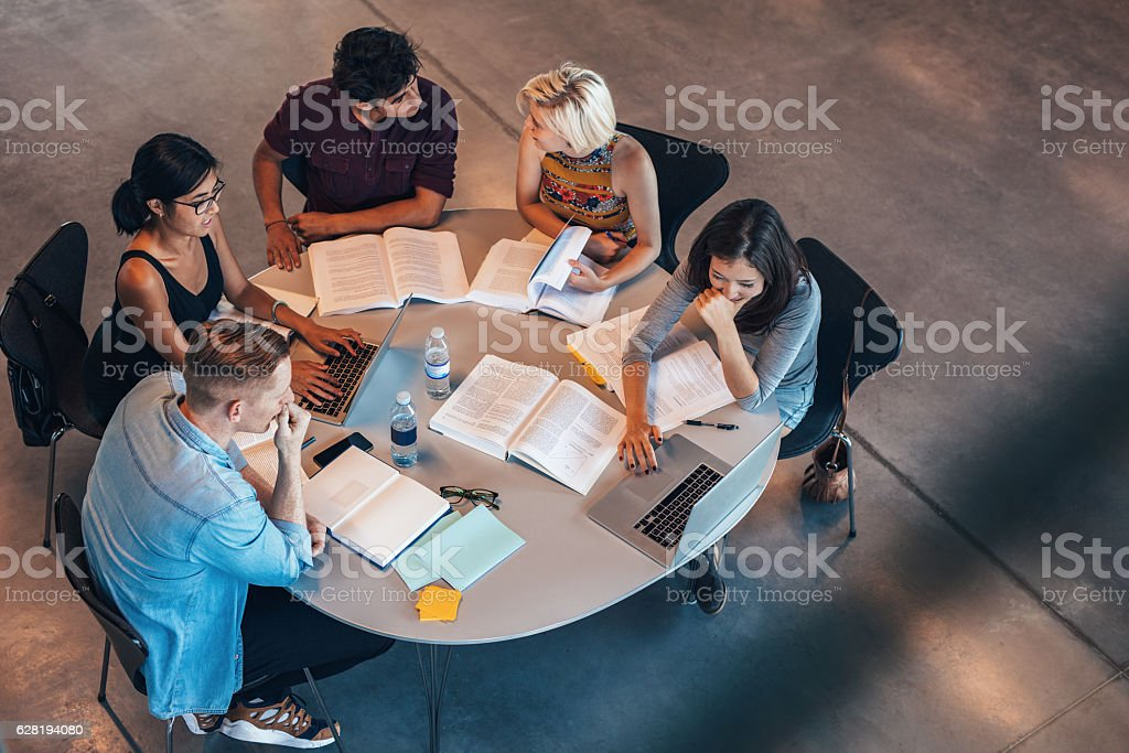 Mixed race students studying together stock photo