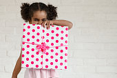 Mixed race sweet little girls holding gift for mother's day. She is four years old. The photo can be use also for father's day, valentine's day, birthdays. The photo was taken in Quebec Canada.