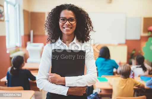 Young teacher in the school building smiling to the camera