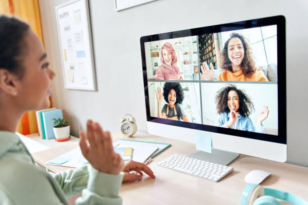自宅でコンピュータを使用してグループ会議距離チャット仮想会議でオンライン仮想チャットビデオ通話中に幸せな多様な十代の友人と話している混合レースの十代の女の子。肩越しの景色� - gen z ストックフォトと画像