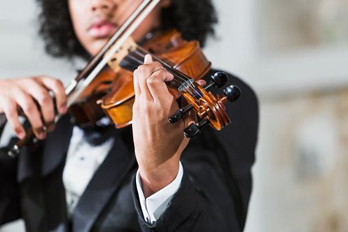 Mixed race teenage boy playing the violin