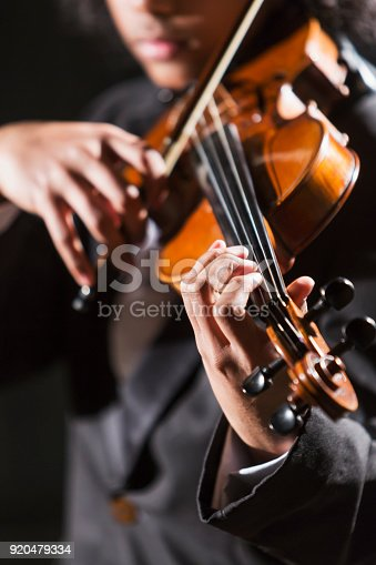 Close-up, cropped view of a mixed race teenage boy, 16 years old, playing the violin, wearing a tuxedo. The focus is on his hand.  He is African-American, Asian and Hispanic.