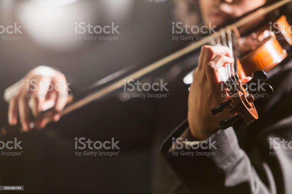 Mixed race teenage boy playing the violin stock photo
