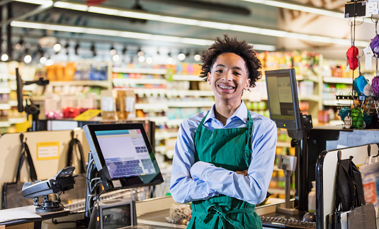 A mixed race African-American and Hispanic teenage boy working in a supermarket at the checkout counter. He is ready to scan groceries at the cash register. He is smiling at the camera.