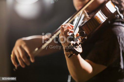 Close-up of a mixed race teenage girl, 15 years old, playing the violin in concert. The focus is on her hand.  She is African-American, Caucasian and Hispanic.