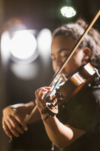 Mixed race teenage girl playing the violin Close-up of a mixed race teenage girl, 15 years old, playing the violin in concert. The focus is on her hand.  She is African-American, Caucasian and Hispanic. child prodigy stock pictures, royalty-free photos & images