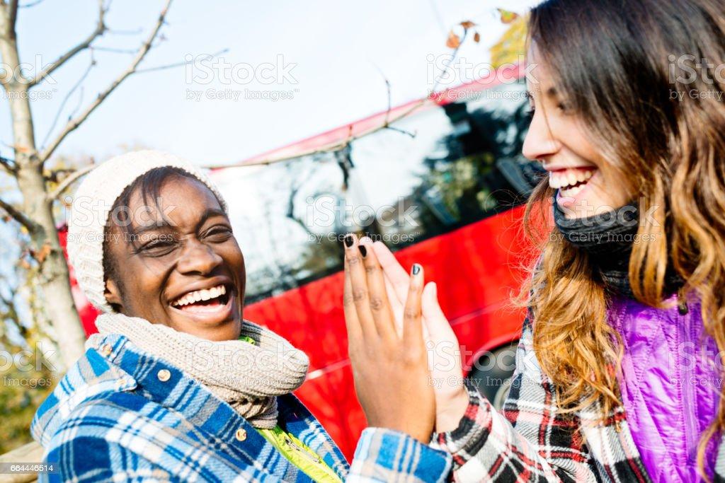Mixed race teenage girls at bus station - foto stock